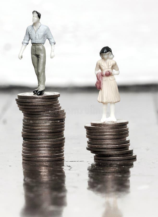 Έννοια ανισότητας αμοιβών με τα αρσενικά και θηλυκά ειδώλια στα νομίσματα στοκ φωτογραφία