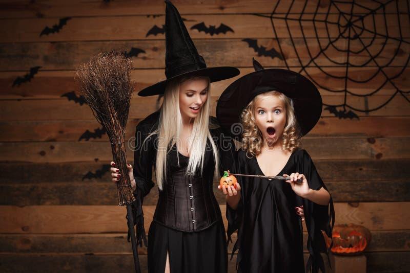 Έννοια αποκριών - η όμορφη καυκάσια μητέρα και η κόρη της στα κοστούμια μαγισσών απολαμβάνουν τη χρησιμοποίηση μαγική με τη μαγικ στοκ φωτογραφίες