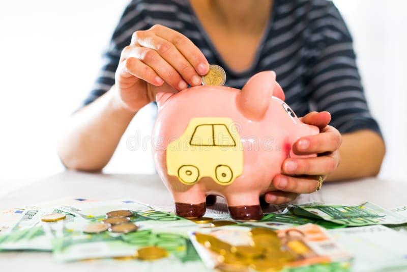 Έννοια αποταμίευσης Το χέρι των γυναικών βάζει τα χρήματα στη piggy τράπεζα Εκλεκτική εστίαση στοκ εικόνες
