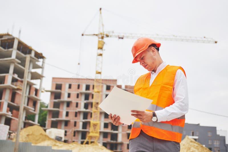 Έννοια αρχιτεκτονικής και εγχώριας ανακαίνισης - άτομο στο κράνος και γάντια με το σχεδιάγραμμα στο εργοστάσιο στοκ εικόνες με δικαίωμα ελεύθερης χρήσης