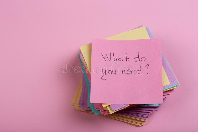 Έννοια βοήθειας και συμβουλών - κολλώδης σημείωση με το κείμενο τι εσείς χρειάζεται στοκ εικόνες
