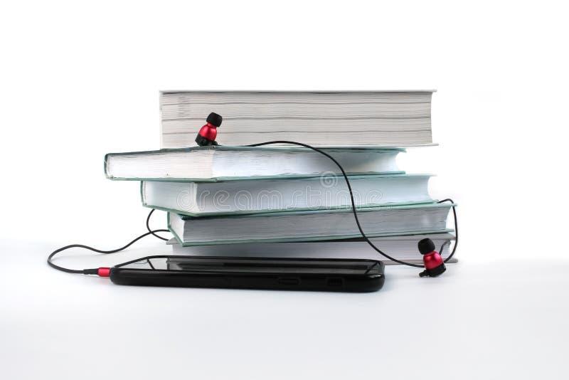 Έννοια για να ακούσει τα audiobooks Κόκκινα ακουστικά και smatphone κοντά στο σωρό των βιβλίων στοκ εικόνα