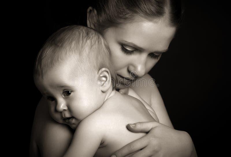Έννοια για την αγάπη και την οικογένεια. μητέρα που αγκαλιάζει το μωρό tenderly στο mon στοκ εικόνες