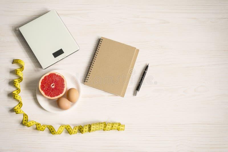 Έννοια γκρέιπφρουτ και διατροφής αυγών Κλίμακα βάρους στο άσπρο ξύλινο υπόβαθρο Τοπ διάστημα άποψης και αντιγράφων στοκ φωτογραφία με δικαίωμα ελεύθερης χρήσης