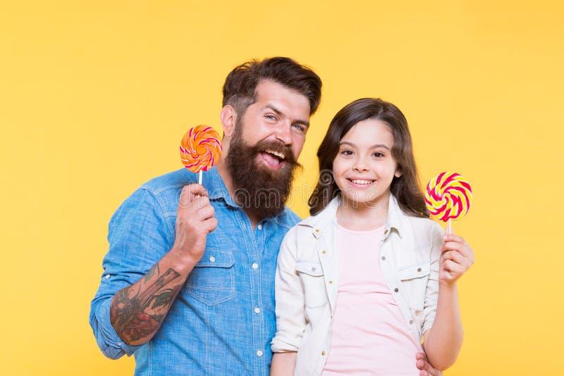 Έννοια γλυκών και απολαύσεων Η κόρη και ο πατέρας τρώνε τις γλυκές καραμέλες Γλυκιά παιδική ηλικία Λαβή παιδιών και μπαμπάδων κορ στοκ φωτογραφία