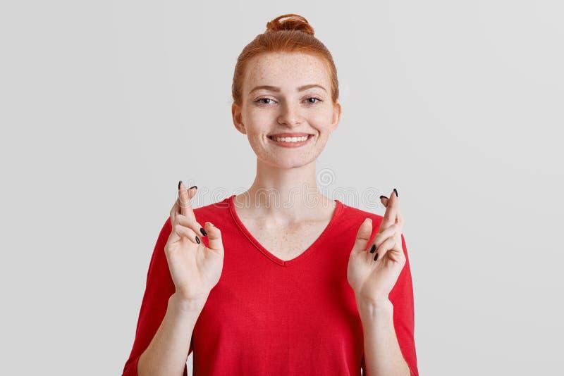 Έννοια γλώσσας του σώματος Η αισιόδοξη φακιδοπρόσωπη κοκκινομάλλης αρκετά γυναίκα σπουδαστής διασχίζει τα δάχτυλα για την καλή τύ στοκ εικόνες