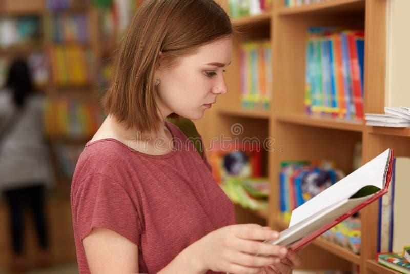 Έννοια γυμνασίου, εκπαίδευσης και εκμάθησης Το κορίτσι σπουδαστών με hairstyle, ντυμένος στην περιστασιακή μπλούζα, κρατά το ανοι στοκ φωτογραφίες