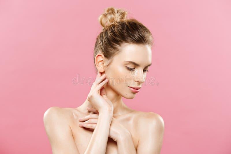 Έννοια δερμάτων ομορφιάς - η όμορφη νέα καυκάσια γυναίκα με το καθαρό φρέσκο δέρμα κοιτάζει μακριά με το ρόδινο υπόβαθρο στούντιο στοκ εικόνες