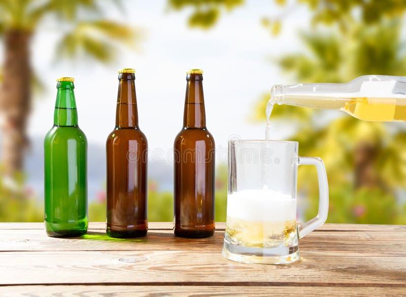 Έννοια διακοπών, θολωμένο τροπικό υπόβαθρο, goblet μπύρας στον ξύλινο πίνακα στοκ φωτογραφία με δικαίωμα ελεύθερης χρήσης