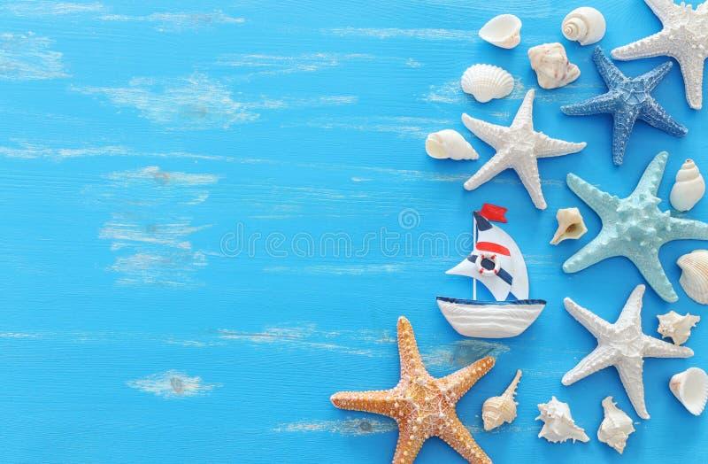 Έννοια διακοπών και καλοκαιριού με τον εκλεκτής ποιότητας αστερία και τα θαλασσινά κοχύλια βαρκών πέρα από το μπλε ξύλινο υπόβαθρ στοκ εικόνα