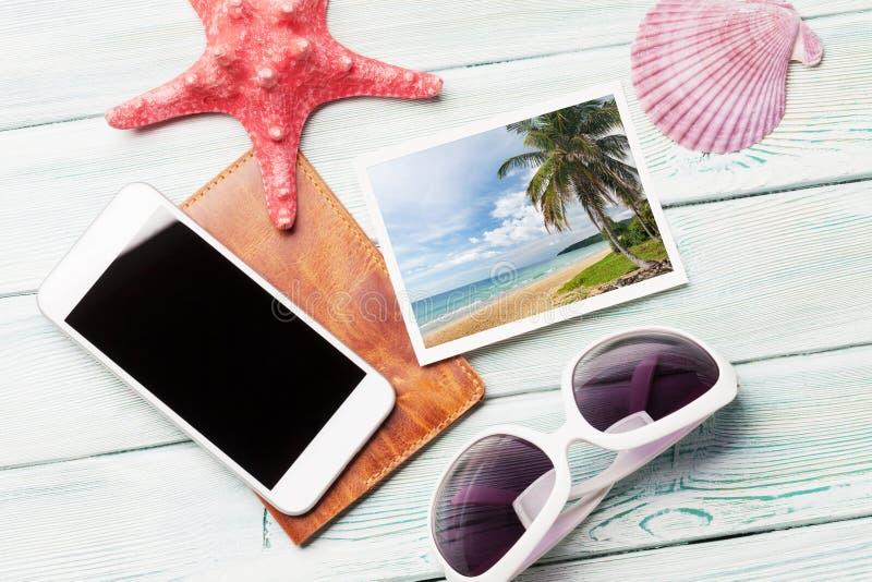 Έννοια διακοπών ταξιδιού με τα γυαλιά ηλίου, τις φωτογραφίες smartphone και Σαββατοκύριακου στο ξύλινο σκηνικό Τοπ όψη Επίπεδος β στοκ εικόνες