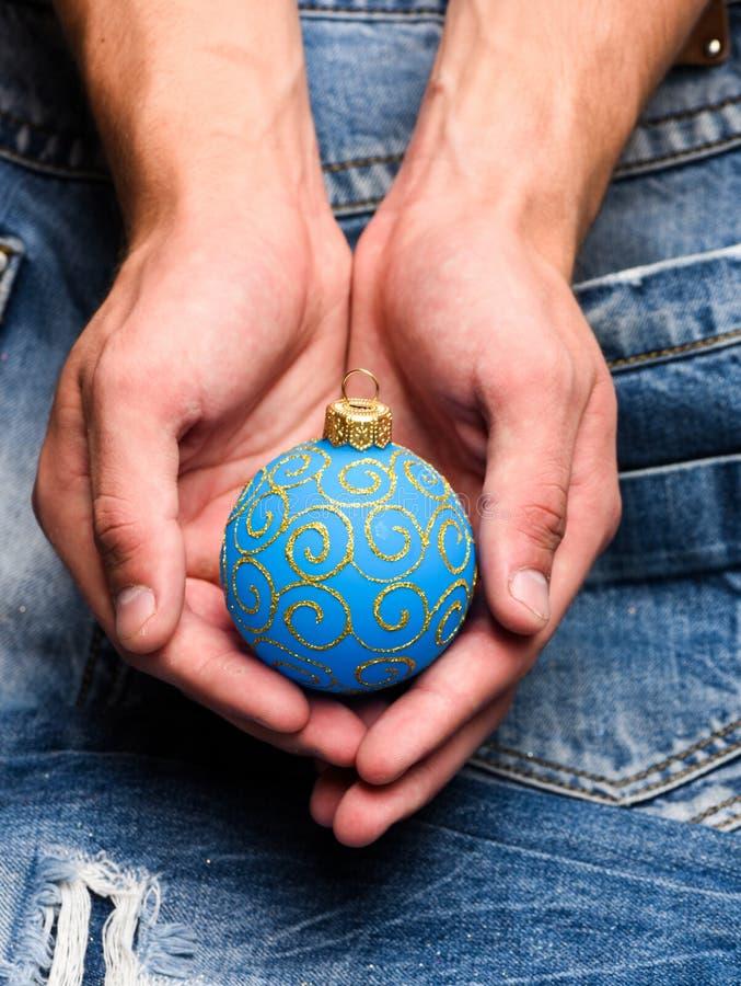 Έννοια διακοσμήσεων Χριστουγέννων Το μπιχλιμπίδι χριστουγεννιάτικων δέντρων παραδίδει μέσα το υπόβαθρο τζιν Η σφαίρα χειμερινών δ στοκ φωτογραφία με δικαίωμα ελεύθερης χρήσης