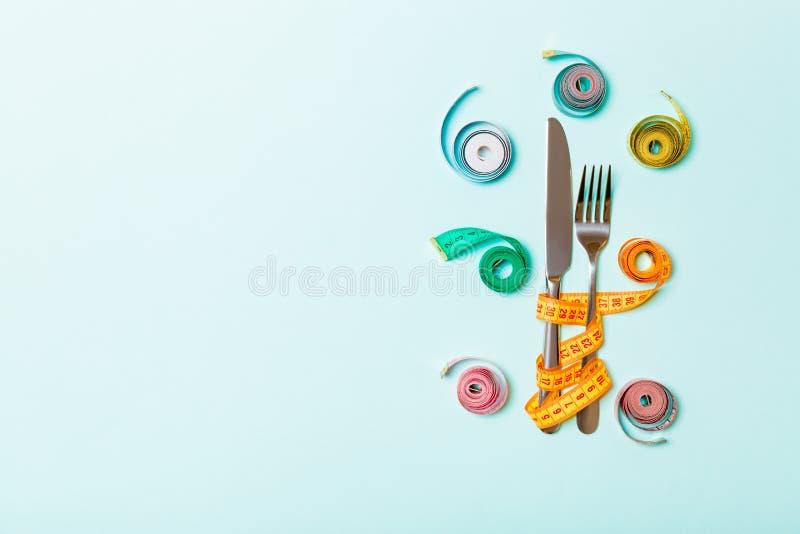 Έννοια διατροφής με το δίκρανο και το μαχαίρι που περιβάλλονται με τις χρωματισμένες μετρώντας ταινίες στο μπλε υπόβαθρο Τοπ άποψ στοκ φωτογραφία με δικαίωμα ελεύθερης χρήσης