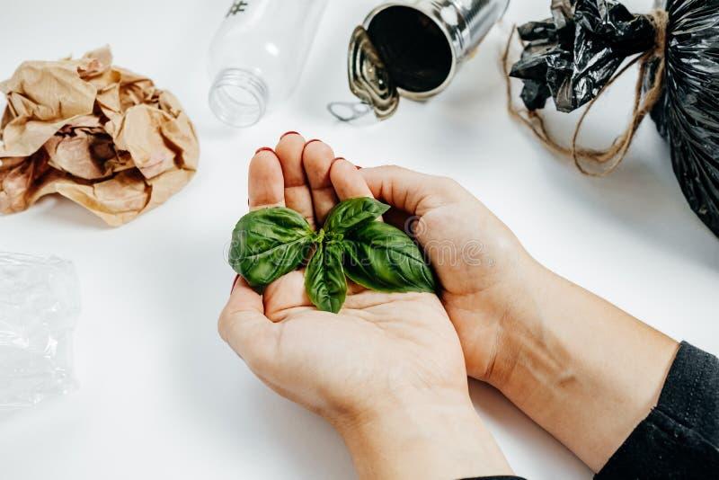 Έννοια διαχείρησης αποβλήτων Χέρια γυναικών με το πράσινο φύλλο και garbag στοκ εικόνα με δικαίωμα ελεύθερης χρήσης