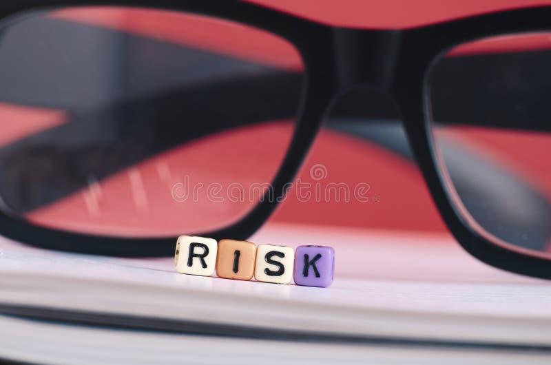 Έννοια διαχείρησης κινδύνων Κύβος λέξης κινδύνου στο βιβλίο πέρα από το κόκκινο backgrou στοκ εικόνα