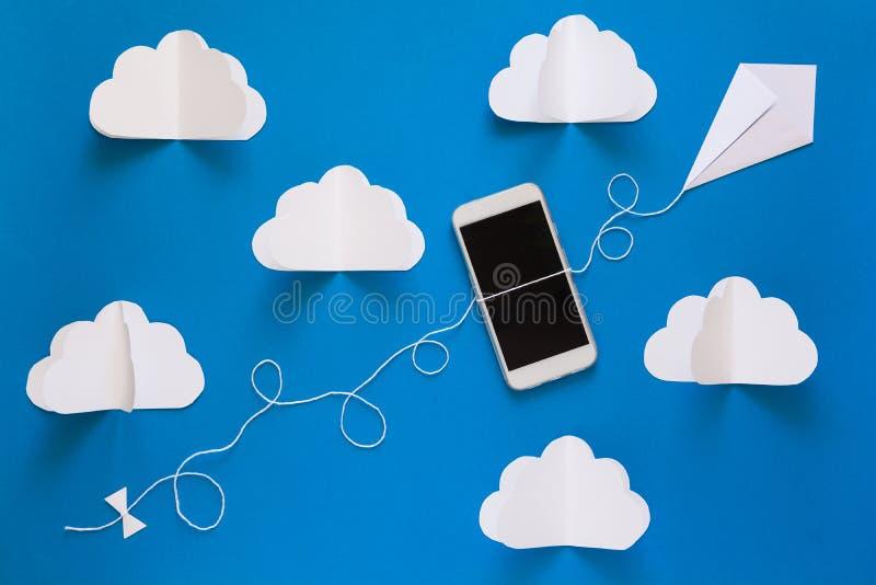 Έννοια δικτύων μεταδόσεων στοιχείων και υπολογισμού σύννεφων Έξυπνο τηλέφωνο που πετά στον ικτίνο εγγράφου στο μπλε ουρανό στοκ φωτογραφίες με δικαίωμα ελεύθερης χρήσης