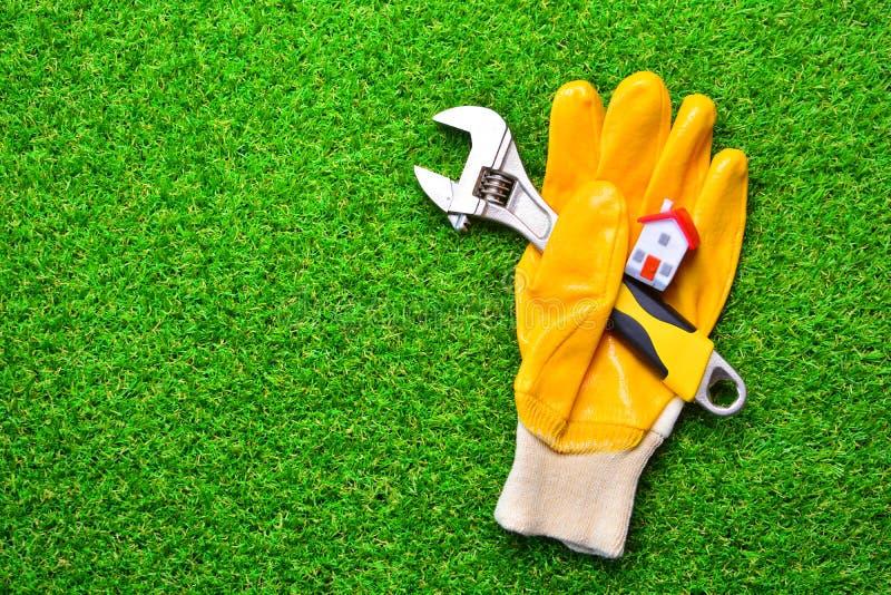 Έννοια εγχώριων επισκευών Να στηριχτεί το γάντι με ένα διευθετήσιμο γαλλικό κλειδί και το μικροσκοπικό σπίτι σε μια πράσινη χλόη στοκ φωτογραφίες