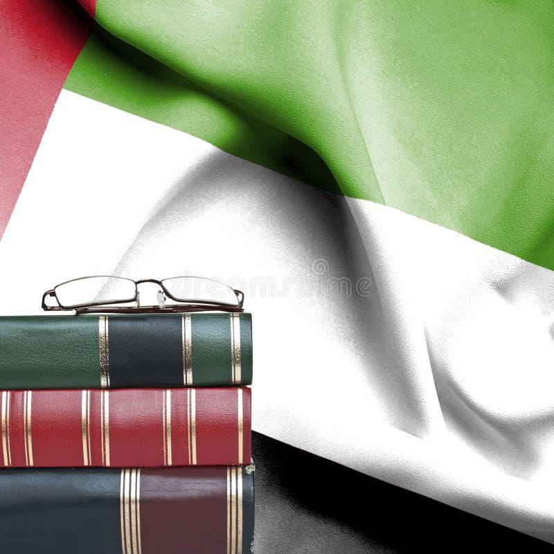 Έννοια εκπαίδευσης - σωρός των βιβλίων και των γυαλιών ανάγνωσης ενάντια στη εθνική σημαία των Ηνωμένων Αραβικών Εμιράτων στοκ εικόνα