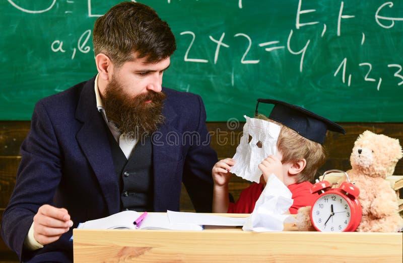 έννοια εκπαιδευτική Όμορφος δάσκαλος και μια μικρή συνεδρίαση αγοριών μπροστά από έναν πράσινο πίνακα Παιδί στο κρύψιμο βαθμολόγη στοκ εικόνα