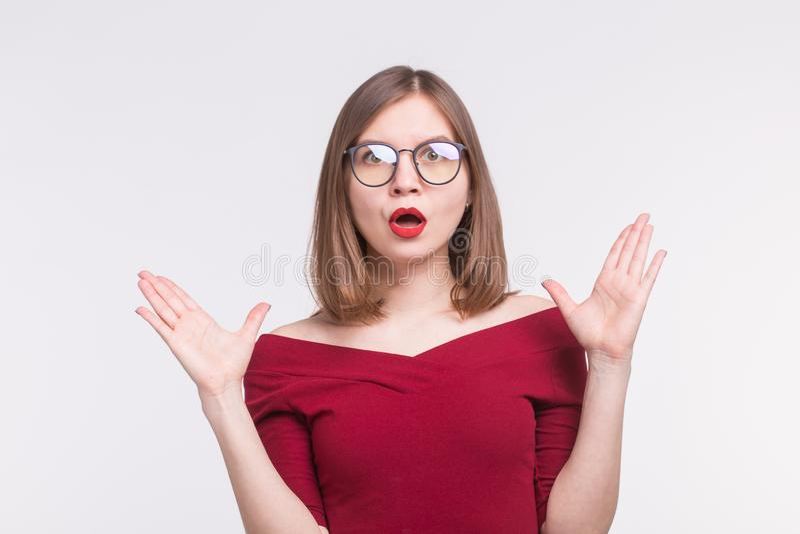 Έννοια εκφράσεων και ανθρώπων - πορτρέτο της νέας συγκλονισμένης γυναίκας στα γυαλιά, χέρια επάνω στο άσπρο υπόβαθρο στοκ φωτογραφία με δικαίωμα ελεύθερης χρήσης