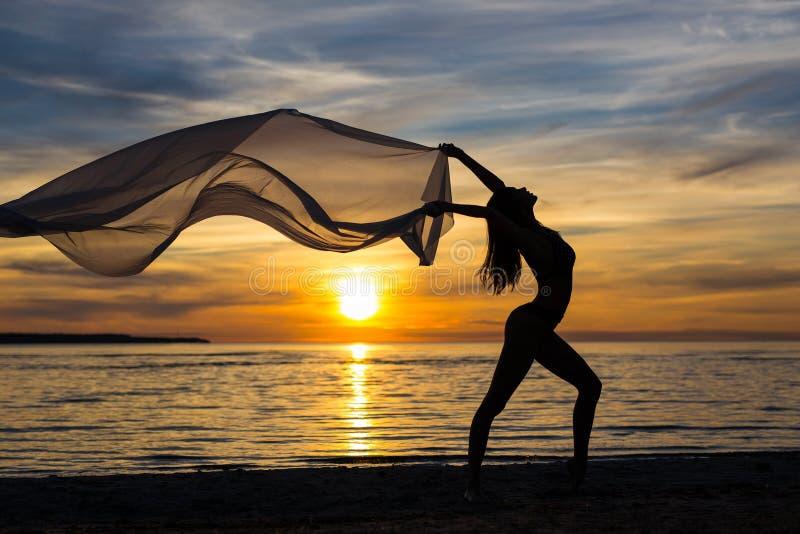 Έννοια ελευθερίας - σκιαγραφία της λεπτής γυναίκας που χορεύει με το μαντίλι επάνω στοκ φωτογραφίες