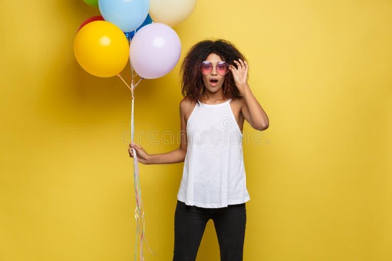 Έννοια εορτασμού - κλείστε επάνω την ευτυχή νέα όμορφη αφρικανική γυναίκα πορτρέτου με την άσπρη μπλούζα που χαμογελά με ζωηρόχρω στοκ εικόνα με δικαίωμα ελεύθερης χρήσης