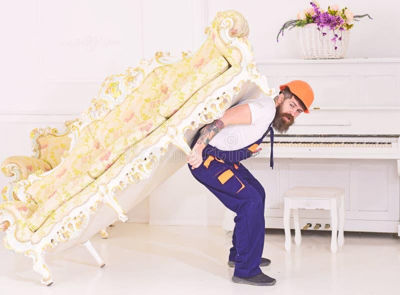 Έννοια επανεντοπισμού Ο φορτωτής κινεί τον καναπέ, καναπές Το άτομο με τη γενειάδα, τον εργαζόμενο στις φόρμες και το κράνος φέρν στοκ φωτογραφία με δικαίωμα ελεύθερης χρήσης