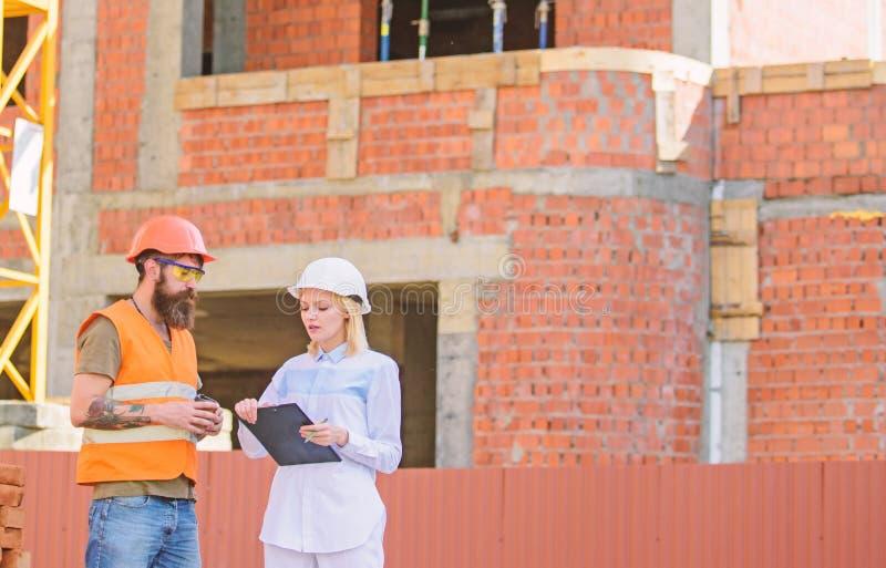 Έννοια επικοινωνίας ομάδων κατασκευής Συζητήστε το σχέδιο προόδου Ο μηχανικός και ο οικοδόμος γυναικών επικοινωνούν το εργοτάξιο  στοκ εικόνες