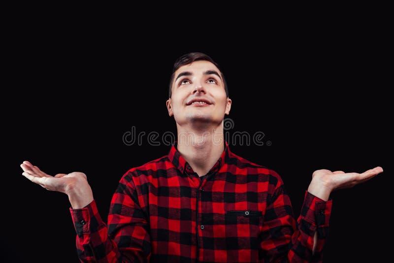 έννοια επιλογής Ο νεαρός άνδρας ανατρέχει με τα χέρια που αυξάνονται στο μαύρο υπόβαθρο Διάστημα για τη διαφήμιση στοκ εικόνα
