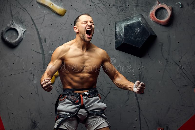 Έννοια επιτυχίας - άτομο που κραυγάζει παρουσιάζοντας τη δύναμη και μυς Ισχυρός ορειβάτης στοκ εικόνες