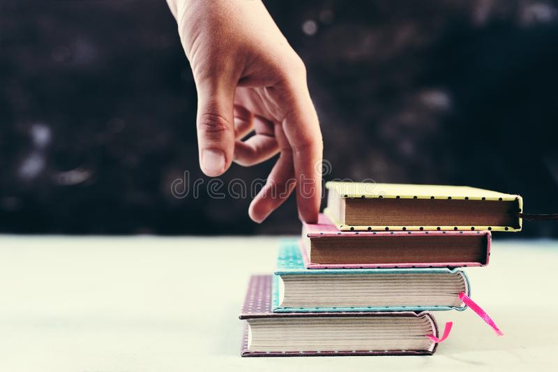 Έννοια επιτυχίας με τα δάχτυλα που αναρριχούνται στα σκαλοπάτια φιαγμένη από σωρό βιβλίων στοκ εικόνα
