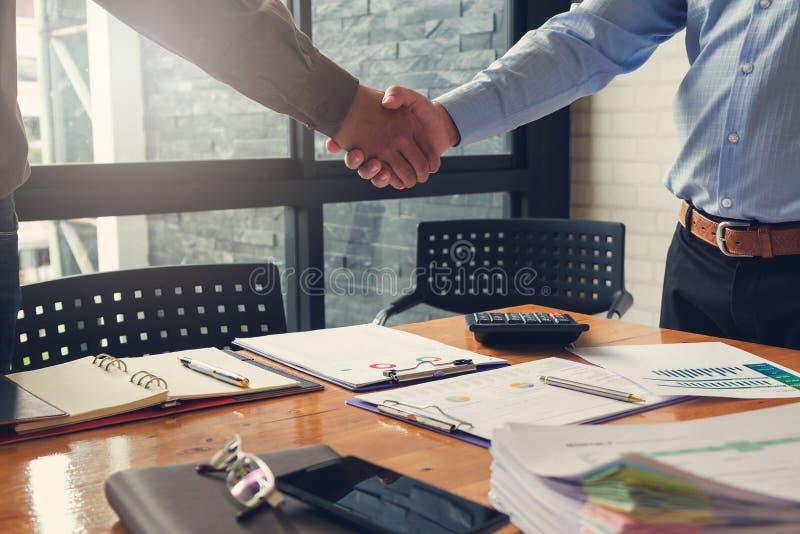 Έννοια επιχειρήσεων και χρηματοδότησης του γραφείου που λειτουργεί, επιχειρηματίες που τινάζουν το χέρι με το συνεργάτη του στοκ εικόνες