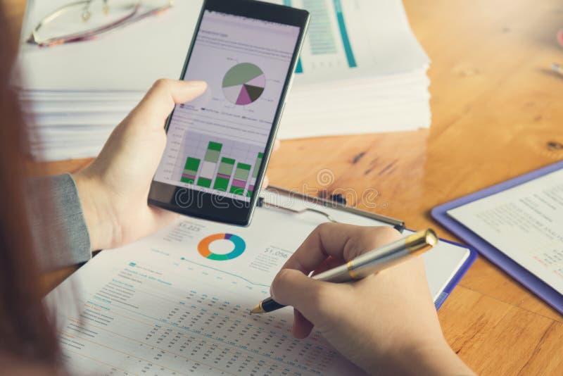Έννοια επιχειρήσεων και χρηματοδότησης του γραφείου που λειτουργεί, επιχειρηματίας που χρησιμοποιεί το έξυπνο τηλέφωνο στη συζήτη στοκ εικόνα