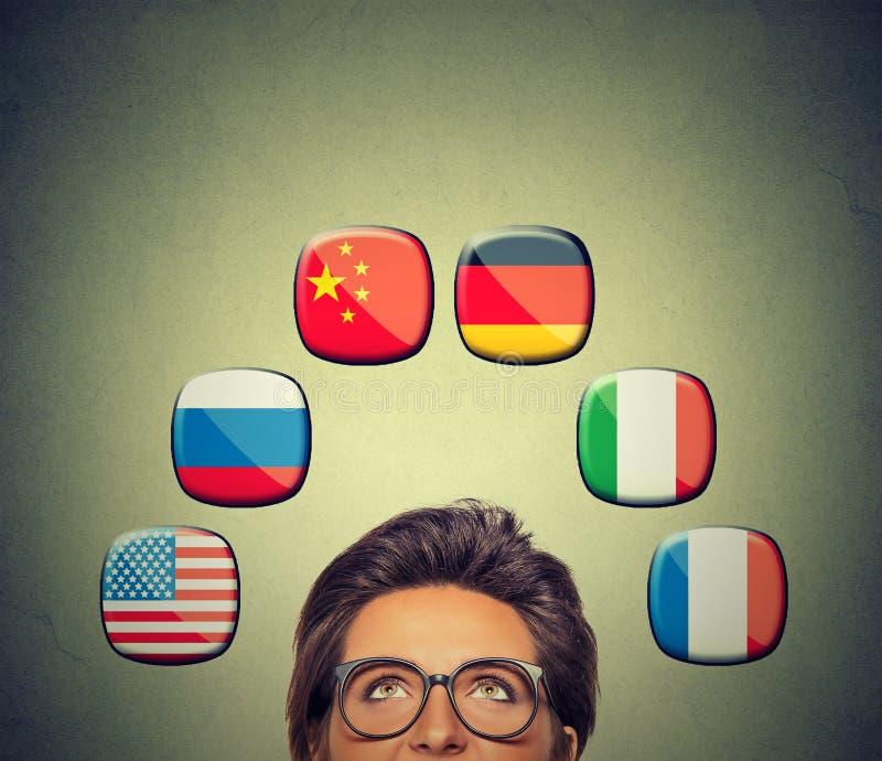 Έννοια ευκαιρίας εργασίας και ταξιδιού Γυναίκα στα γυαλιά που εξετάζει επάνω τα εικονίδια των διεθνών σημαιών απεικόνιση αποθεμάτων