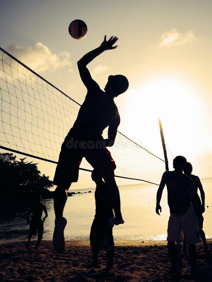 Έννοια ελεύθερου χρόνου αθλητικής παίζοντας άσκησης ηλιοβασιλέματος πετοσφαίρισης παραλιών στοκ εικόνα