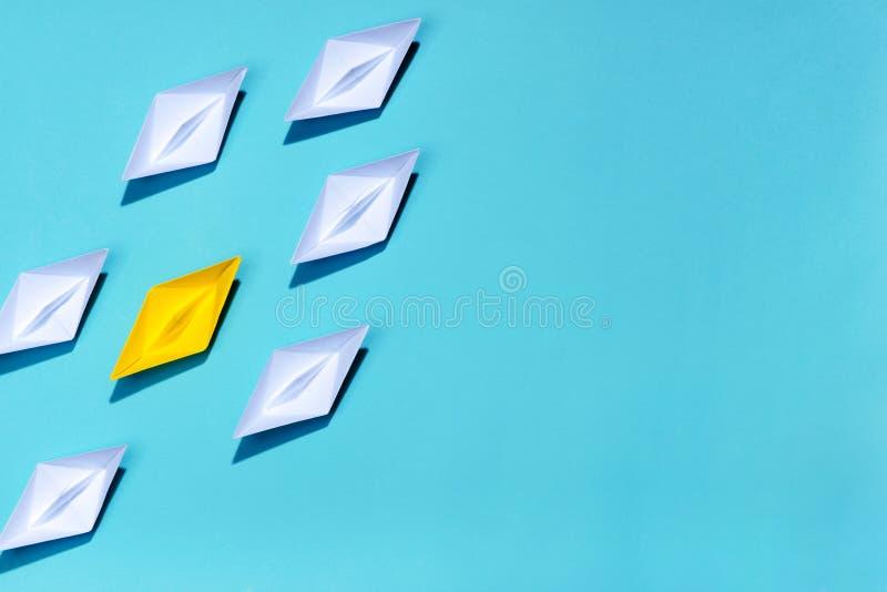 Έννοια ηγεσίας Κίτρινο σκάφος εγγράφου που οδηγεί μεταξύ του λευκού στοκ εικόνες