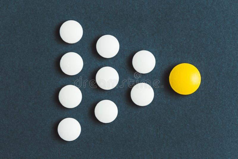 Έννοια ηγεσίας με το κίτρινο χάπι που οδηγεί μεταξύ του λευκού στο μπλε υπόβαθρο στοκ εικόνα με δικαίωμα ελεύθερης χρήσης