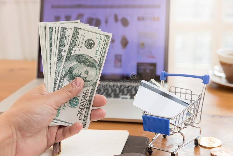 Έννοια ηλεκτρονικού εμπορίου, χρήματα εκμετάλλευσης χεριών και πιστωτική κάρτα στο κάρρο αγορών με το ανοικτό υπόβαθρο ιστοχώρου  στοκ φωτογραφία με δικαίωμα ελεύθερης χρήσης