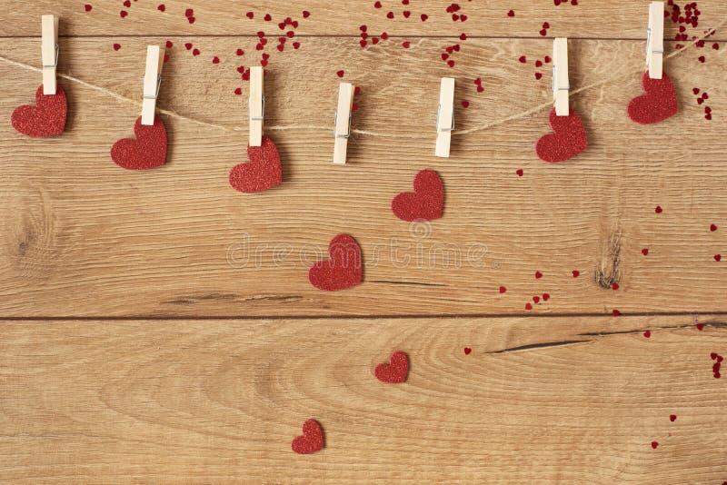 Έννοια ημέρας βαλεντίνων ` s Γιρλάντα μορφής καρδιών Το κόκκινο ακτινοβολεί καρδιές που κρεμούν στο σχοινί στο ξύλινο υπόβαθρο στοκ φωτογραφίες