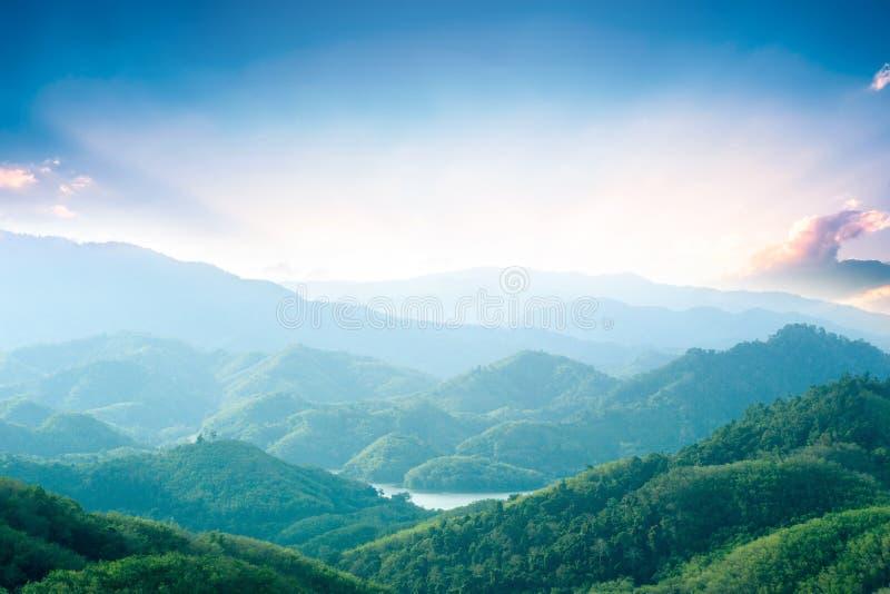 Έννοια ημέρας παγκόσμιου περιβάλλοντος: Πράσινα βουνά και όμορφα σύννεφα ουρανού κάτω από το μπλε ουρανό στοκ φωτογραφία