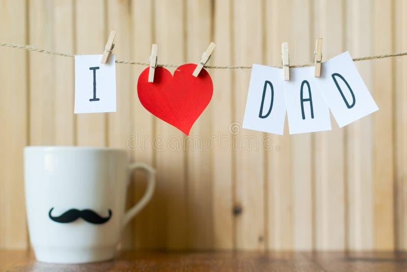 Έννοια ημέρας πατέρων Μήνυμα χαιρετισμού με την ένωση καρδιών εγγράφου με τα clothespins πέρα από τον ξύλινο πίνακα Χρόνια πολλά στοκ εικόνα