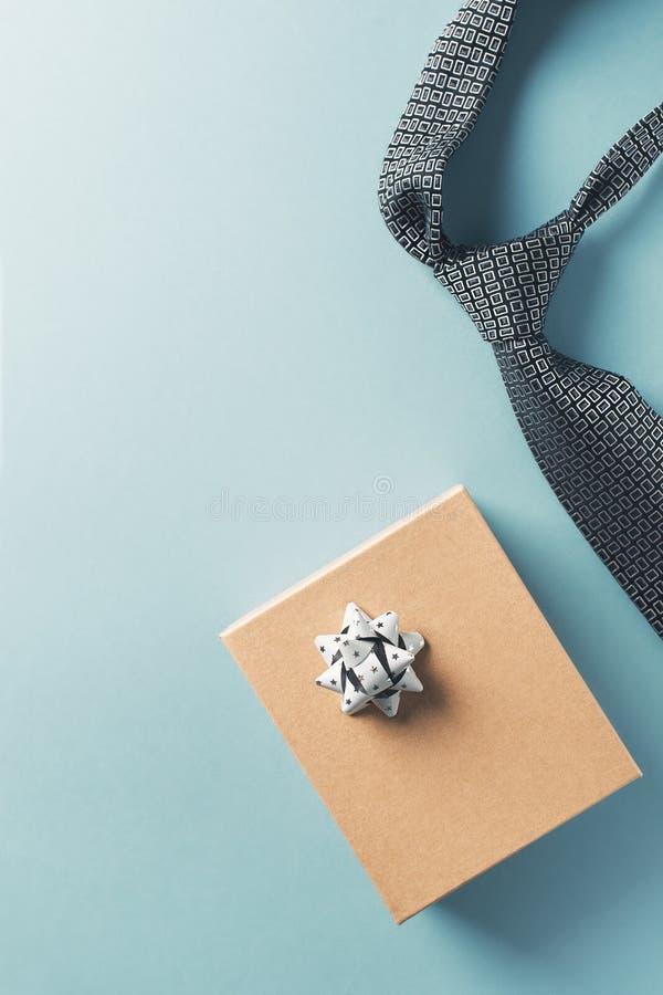 Έννοια ημέρας πατέρων με το κιβώτιο δώρων και δεσμός στο μπλε υπόβαθρο στοκ εικόνα