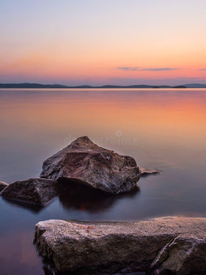 Έννοια ηρεμίας και περισυλλογής Ηλιοβασίλεμα στη λίμνη, βράχοι στο πρώτο πλάνο, ήρεμο νερό, ασυννέφιαστος ουρανός στοκ εικόνες