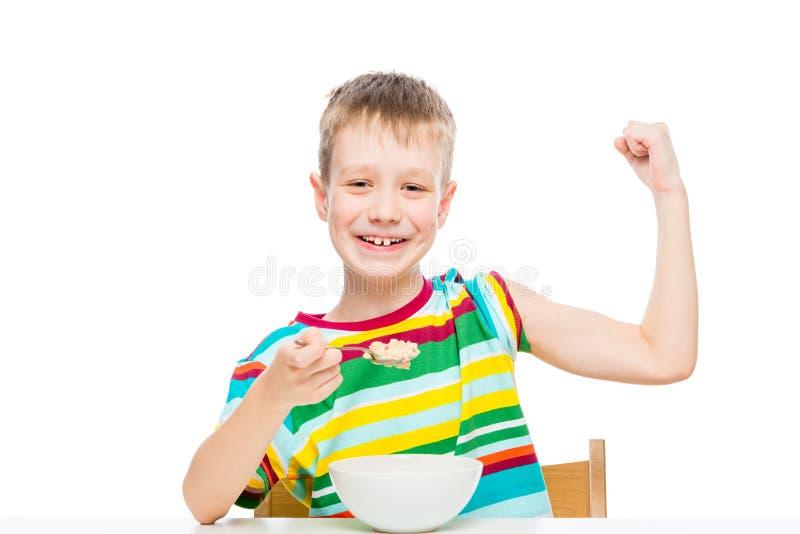 έννοια - η κατάλληλη διατροφή, ένα ισχυρό υγιές αγόρι παρουσιάζει δικέφαλους μυς στοκ εικόνα