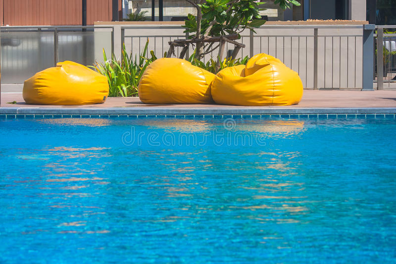 Έννοια διακοπών και χαλάρωσης: Κίτρινο στρώμα τρία στην άκρη της πισίνας στο θέρετρο στοκ φωτογραφία με δικαίωμα ελεύθερης χρήσης