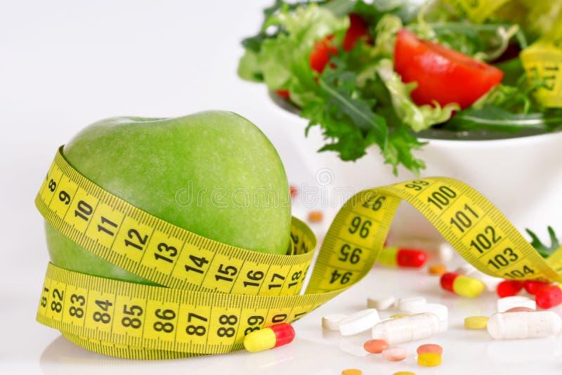 Έννοια διατροφής - πράσινη μήλο, ταμπλέτα, μέτρο ταινιών και μαρούλι στοκ εικόνα