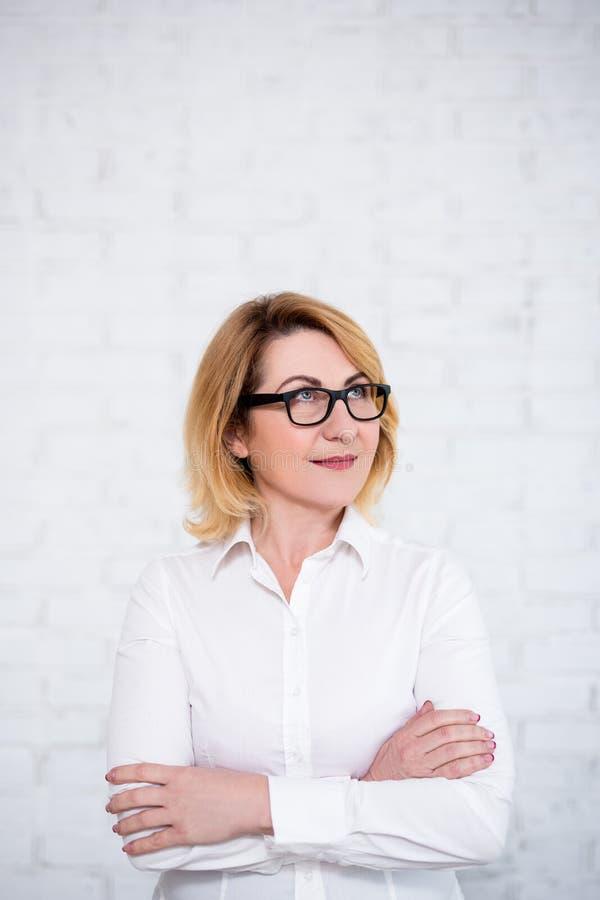 Έννοια ιδέας - ώριμη επιχειρησιακή γυναίκα eyeglasses που κοιτάζει επάνω στο μυρμήγκι που σκέφτεται για κάτι πέρα από τον άσπρο τ στοκ εικόνα