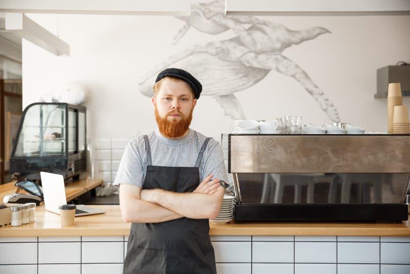Έννοια ιδιοκτητών επιχείρησης καφέ - πορτρέτο του ευτυχούς νέου γενειοφόρου καυκάσιου barista στην ποδιά με τη βέβαια εξέταση στοκ φωτογραφία