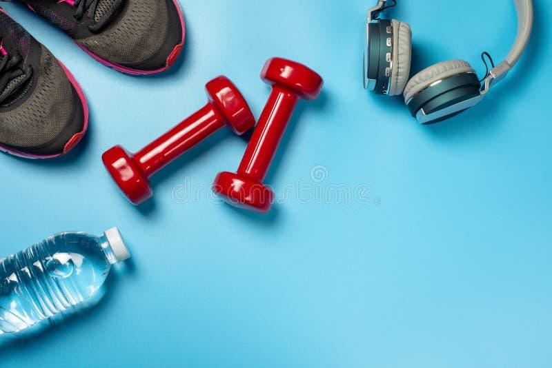 Έννοια ικανότητας και υγειονομικής περίθαλψης των κόκκινων αλτήρων, των παπουτσιών αθλητών, των ακουστικών και του μπουκαλιού νερ στοκ εικόνα