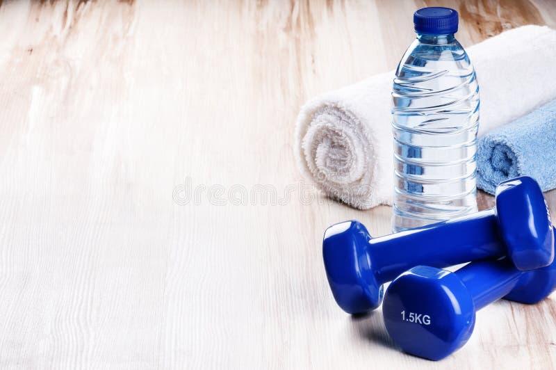 Έννοια ικανότητας με τους αλτήρες και το μπουκάλι νερό στοκ εικόνες